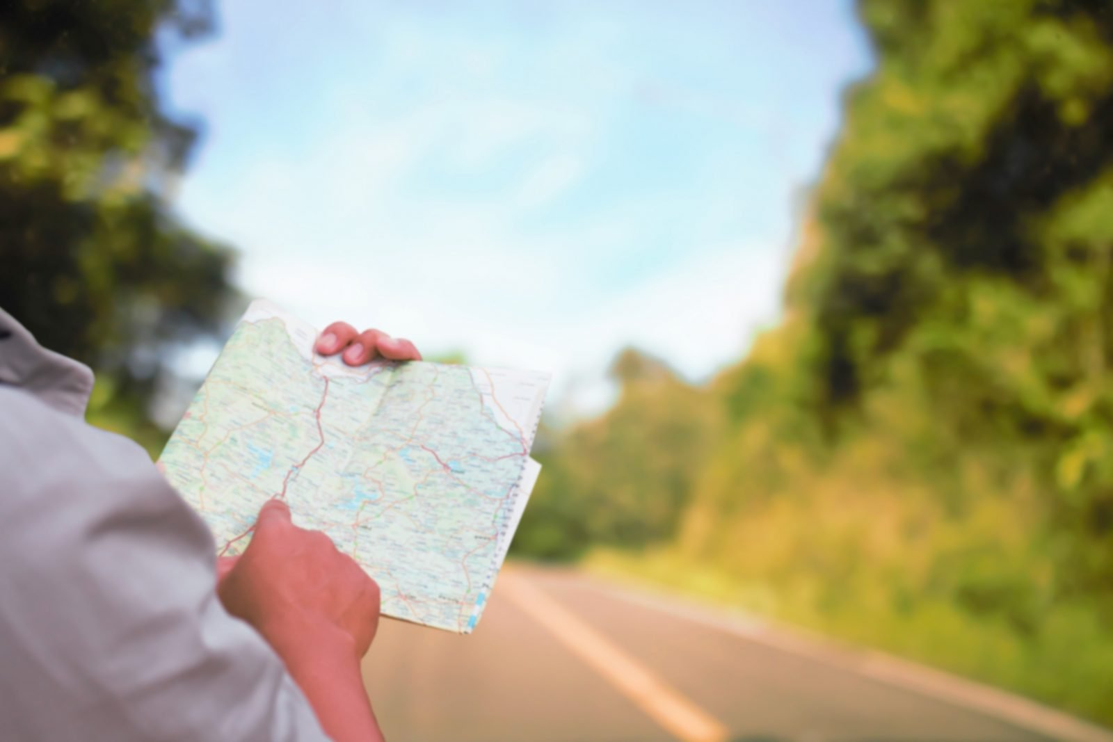 Image of someone who is standing mostly off screen to the left holding a map in front of of a road with trees to the right